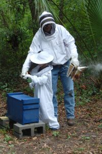 Man and kid in bee suits working on hive